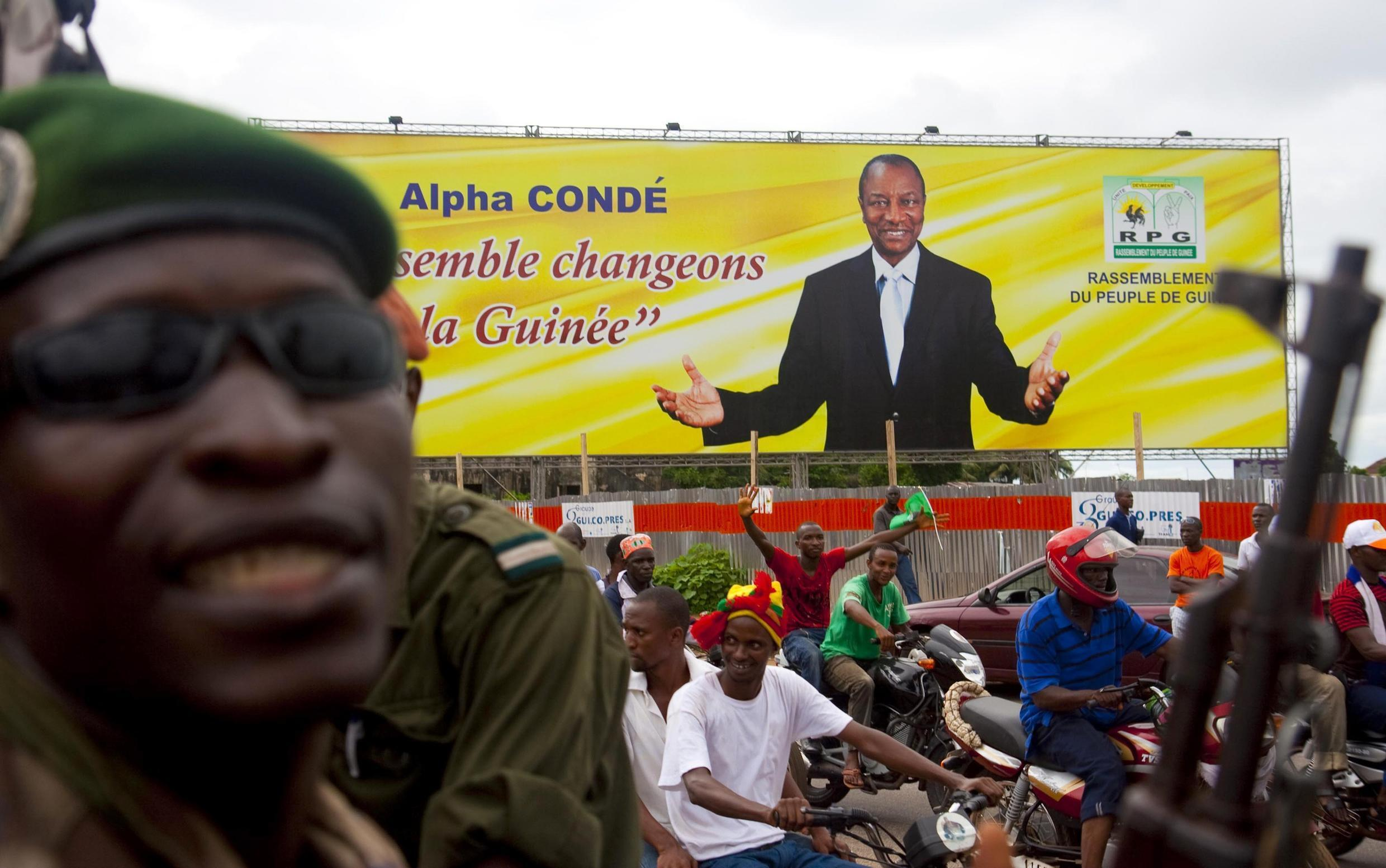 A gendarme stands near a poster of Guinea's presidential candidate Alpha Conde at a rally in Conakry, 19 October