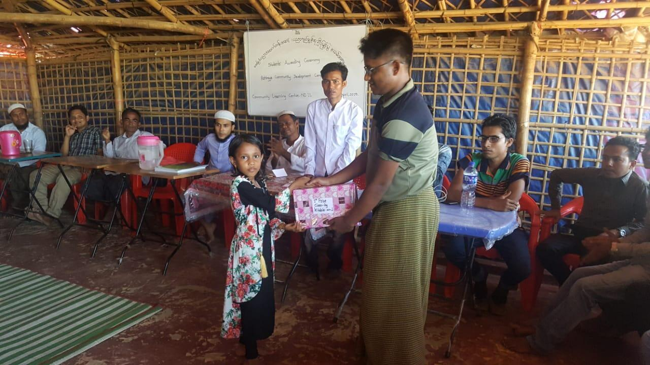 Khin Maung awards first prize to the girl who came top of her class at Thayin Khali Rohingya refugee camp.
