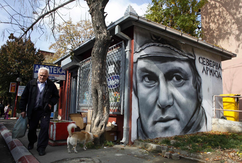 Morador da cidade de Zevecan caminha ao lado do grafite feito a partir do rosto do general sérvio Ratko Mladic.