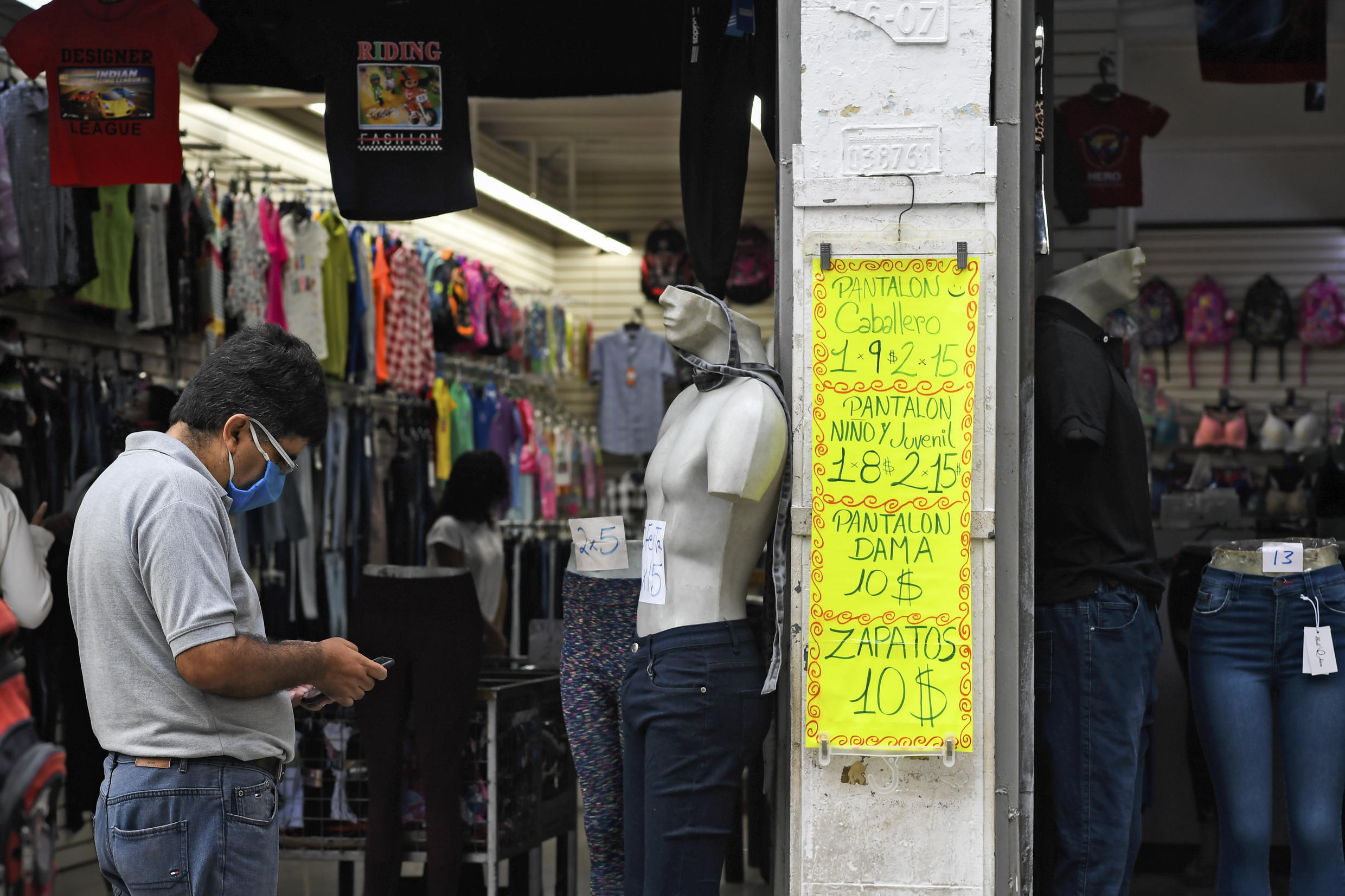 A man uses a mobile phone in front of a sign displaying prices in US dollars in December 2020 outside a clothing store in Venezuela's capital Caracas, which has been ravaged by hyperinflation and other economic problems