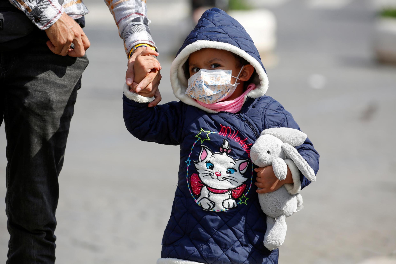 Criança usa máscara perto do Coliseu, em Roma