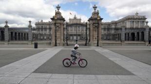 Une petite fille fait du vélo devant le Palais royal à Madrid, le 26 avril 2020.