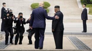 O Presidente dos Estado Unidos Donald Trump e o líder norte-coreano, de costas em Panmunjom,na zona que separa a fronteira entre a Coreia do Norte e a Coreia do Sul.  30 de Junho de 2019