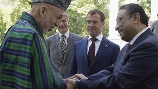 Hamid Karzai (L) greets Asif Ali Zardari (R) as President Dmitry Medvedev (2nd R) looks on