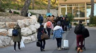 Un grupo de ciudadanos franceses abandona el complejo vacacional próximo a Marsella donde cumplieron una cuarentena tras su repatriación de China por el coronavirus, el 14 de febrero de 2020 en Carry-le-Rouet, al sureste de Francia