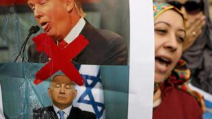 一名巴勒斯坦妇女手持海报抗议美以两国领导人的资料图片