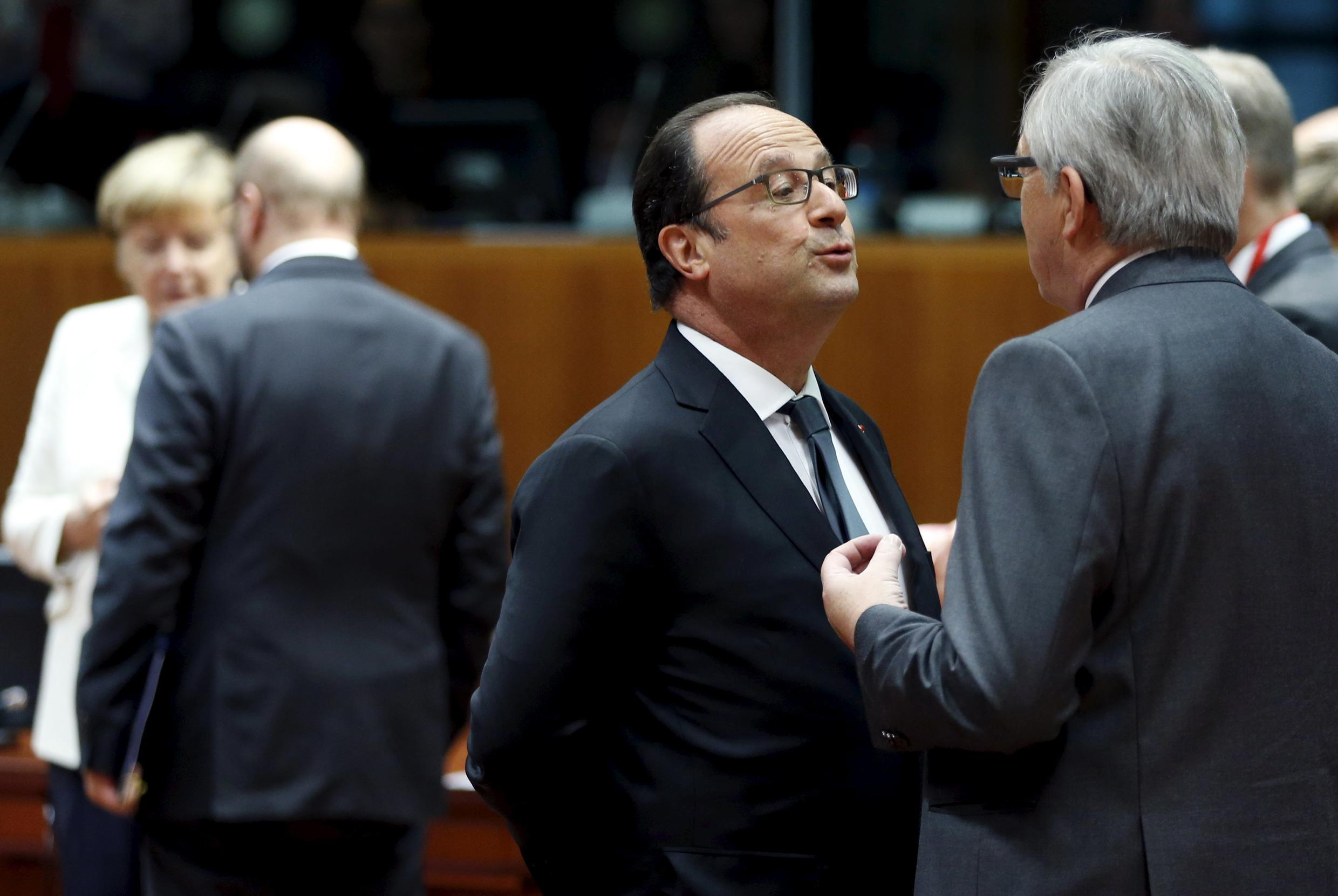 France's President Francois Hollande talks to European Commission President Jean-Claude Juncker (R) next to Germany's Chancellor Angela Merkel and European Parliament President Martin Schulz (L) on Monday