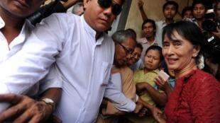Aung San Suu Kyi é acompanhada por partidários em zona de voto.