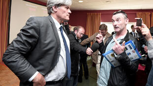 French Agriculture Minister Stéphane Le Foll with a pig farmer last week