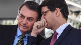 El ministro brasileño de Medio Ambiente, Ricardo Salles (D) le habla al oído al presidente Jair Bolsonaro durante una ceremonia militar celebrada el 11 de octubre de 2019 en Sao Paulo
