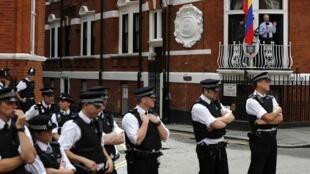 Faute de pouvoir l'arrêter, les bobbies londoniens écoutent Julian Assange s'exprimer depuis le balcon de l'ambassade équatorienne, dimanche 19 août 2012.