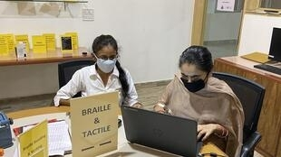 A visually impaired instructor taking online classes for Indian students.