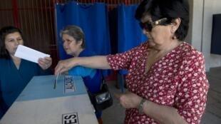 Une habitante de Santiago, glisse son bulletin de vote dans l'urne, lors des élections municipales, le 28 octobre 2012.