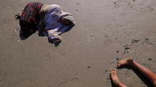 Người tị nạn Rohingya ngã quỵ trên bãi biển Shah Porir Dwip, gần  Cox's Bazar, Bangladesh. Ảnh 1/10/2017.