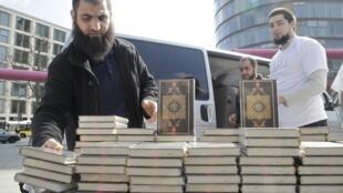 Un membre du mouvement salafiste dispose des Corans sur un étalage près de la Potsdamer Platz, à Berlin, le 14 avril 2012.