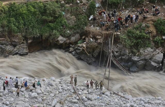 Soldados tentam consertar ponte destruída pelas águas em Govindghat, no Estado de Uttarakhand, no Himalaia.