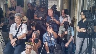 Los fotógrafos esperan pacientes el comienzo del desfile.