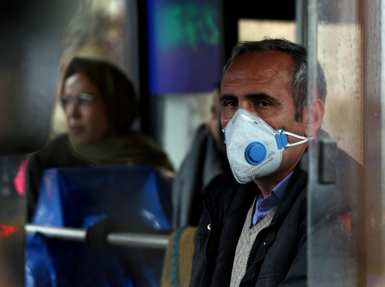 در ایران برخی شهروندان تلاش میکنند با گذاشتن ماسک از ابتلا خود به ویروس کرونا پیشگیری کنند. در این تصویر مردی در یکی از اتوبوسهای عمومی شهر تهران دیده می شود - ٢۵ فوریه ٢٠٢٠