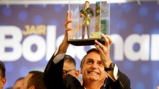 O candidato Jair Bolsonaro (PSL) segura um boneco de si mesmo em Curitiba, em 29 de março de 2018.