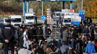 Des gardes-frontière bosniens et croates face à des migrants, à Maljevac, le 24 octobre 2018.