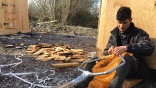 Camp de Grande-Synthe. Zana, un des occupants du camp bricole un filet de pêche. La pêche est un loisir qui lui permet de «tuer» le temps.