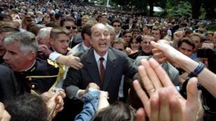 Le président français Jacques Chirac accueille les Français invités à la traditionnelle «garden party» qui suit le défilé militaire du 14 juillet au palais de l'Elysée, le 14 juillet 1997.