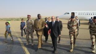 Le ministre de la Défense Jean-Yves Le Drian (au centre à droite) a été reçu par le gouverneur de Faya-Largeau (au centre à gauche) à la descente de l'avion, le 24 février 2017.