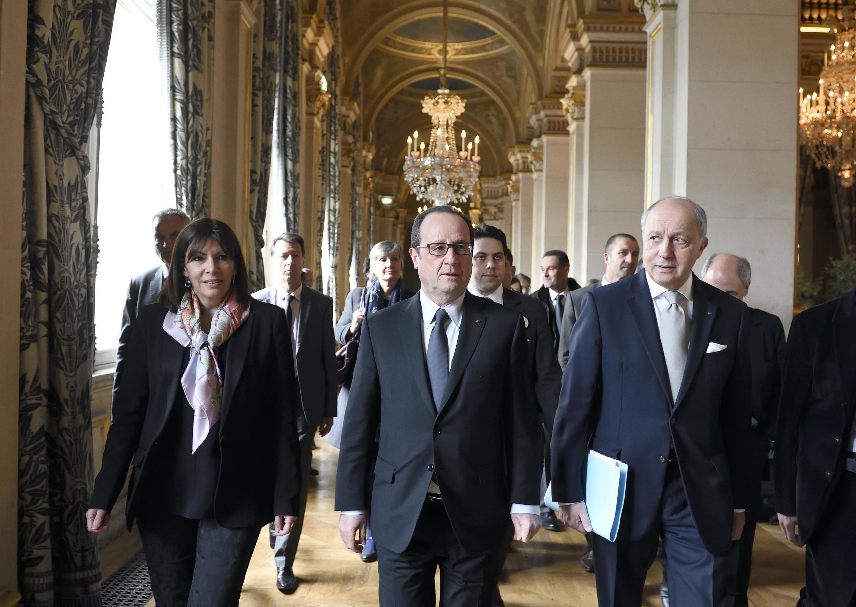 Le président de la République François Hollande entouré de la maire de Paris Anne Hidalgo et du ministre des Affaires étrangères Laurent Fabius, le 26 mars 2015 à l'Hôtel de ville de Paris.