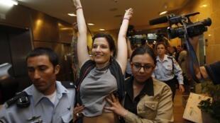 Polícia israelense acompanha manifestante pró-Palestina no aeroporto internacional de Ben Gurion, em Tel Aviv, neste domingo.
