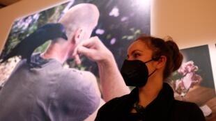 La photographe Francesca Todde devant un grand tirage de son portrait de Tristan Plot avec la corneille Bayo.  © Siegfried Forster / RFI