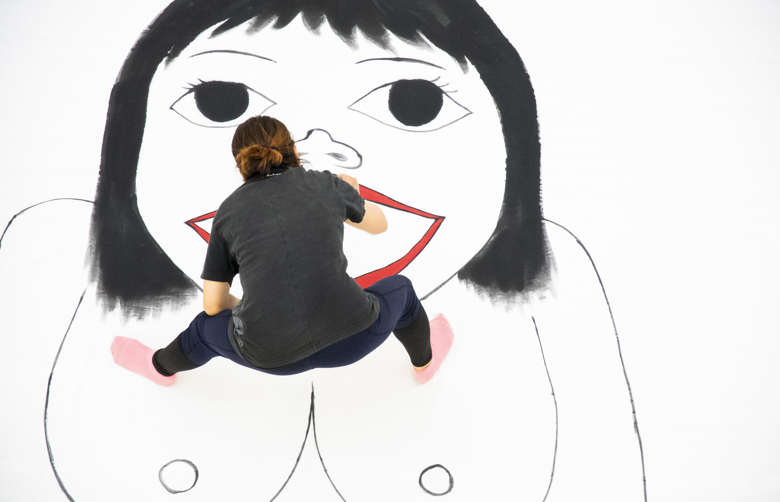 Artist Kubra Khademi from Afghanistan completes one of her portraits in the Visions of Exile Festival in Paris
