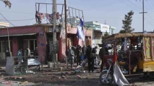 Des Afghans se tiennent près du lieu où la bombe a explosé, sur le marché de Maïmana.