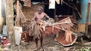 Un habitant déblaye les débris après le passage du cyclone. Port-Vila, le 15 mars 2015.