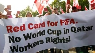 """Biểu tình do Liên đoàn lao động Thụy Sĩ tổ chức tại Zurich, phản đối tổ chức Cúp bóng đá tại Qatar, 03/10/2013. Khẩu hiệu trong ảnh : """"Thẻ đỏ cho FIFA""""."""