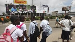 Students stand near a poster of Ouattara in Abidjan, 18 October