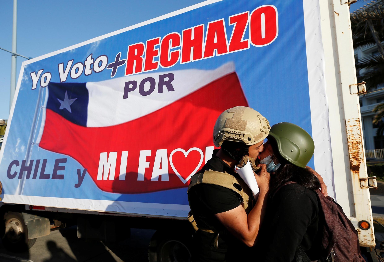 Des militants s'embrassent à côté d'une banderole indiquant «Je vote pour le Chili et ma famille» lors d'un rassemblement, avant le référendum à Vina del Mar, le 22 octobre 2020.