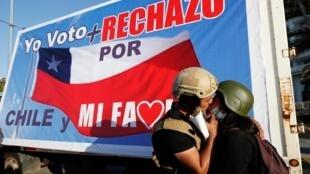 Des militants s'embrassent à côté d'une banderole indiquant «Je vote pour le Chili et ma famille» lors d'un rassemblement avant le référendum, à Vina del Mar, le 22 octobre 2020.