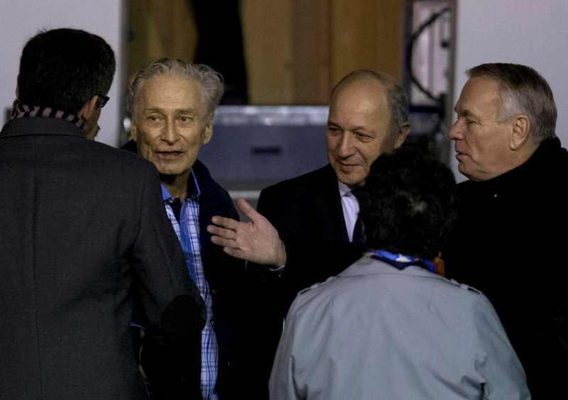 Former French hostage Francis Collomp (2ndL) is welcomed by relatives and officials including Prime Minister Jean-Marc Ayrault (R) and Foreign Affairs minister Laurent Fabius on the tarmac upon his arrival at Villacoublay military airport, near Paris, Nove