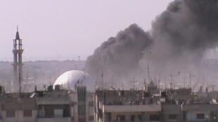 Fumaça no meio de imóveis em Al Khalidieh, perto de Homs.