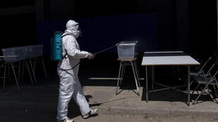 A worker disinfects a polling station on the eve of Chile's constitutional referendum