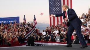 Le président américain jette des masques à ses partisans à son arrivée à son premier meeting de campagne depuis son infection au Covid-19, le 12 octobre à Sanford en Floride.