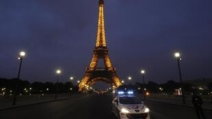 Un auto de la policía delante de la Torre Eiffel.