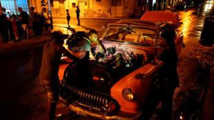 Carlos Ochoa (en la mitad) es 'cuentapropista' y arregla autos en La Habana.