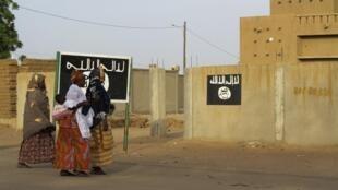 Deux femmes passent devant des pancartes installées par le Mujao, à Gao, le 7 septembre 2012.