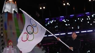 Shim Jae-kook, el alcalde de Pyeonchang clausura los Juegos Olímpicos de Invierno 2018 portando la bandera olímpica en la mano.