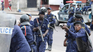 Des policiers réagissant à un jet de pierre depuis le site de la cathédrale Notre Dame à Kinshasa, en RDC ce 25 février 2018.