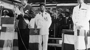 Photo datée de juillet 1960, année de l'indépendance de la République centrafricaine, de David Dacko, président, prononçant un discours devant le lieutenant Jean-Bedel Bokassa (C), attaché militaire à la présidence.