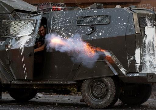 Un policía antidisturbios dispara hacia los manifestantes durante una protesta en 22 de Noviembre de 2019 en Santiago.