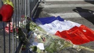 图为尼斯英国海滨大道恐怖袭击案现场上民众悼念受害者国旗与鲜花