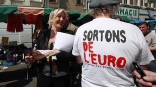 """Marine Le Pen  campaigns at an open-air market in Henin-Beaumont May 29, 2012; T-shirt reads, """"Leave the Euro"""""""